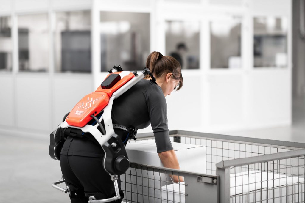 Woman demonstrates the use of an exoskeleton when lifting heavy loads