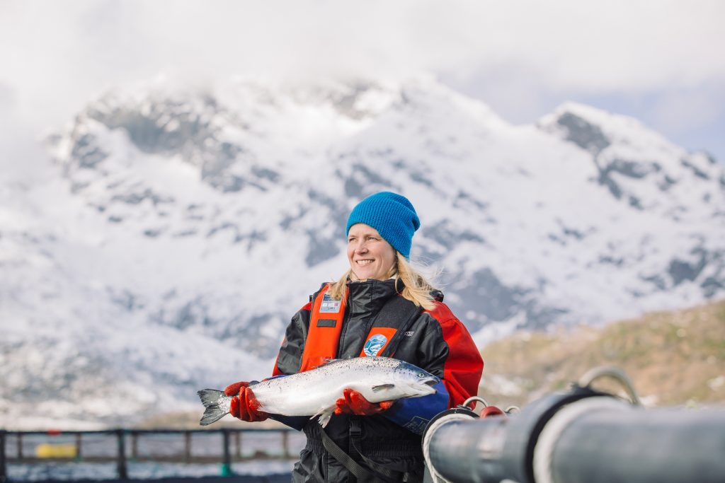 Woman holds freshly caught salmon in Norway