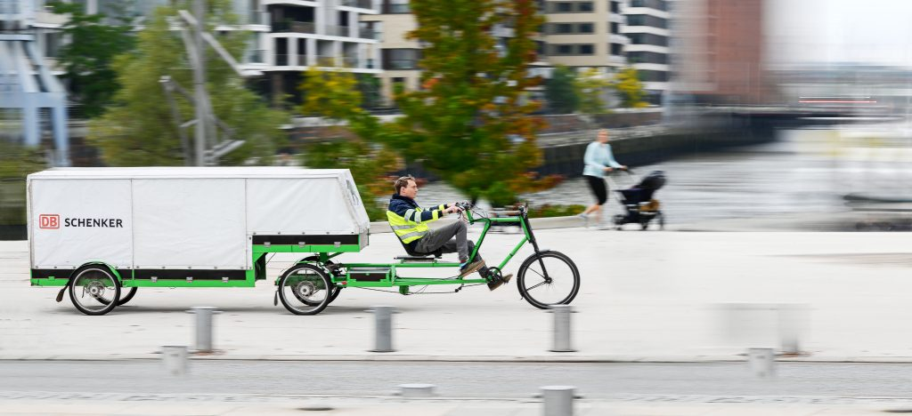 Person is driving a large Cargo Bike in the city of Hamburg