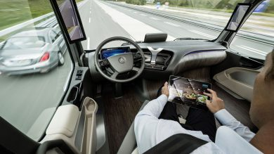 Driver is sitting in an autonomous truck which is driving on a highway.
