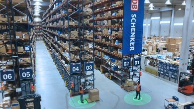 Birdseye view of employees using social distancing wearables in a warehouse