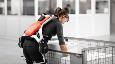 Innovation and technology in warehousing - woman uses exoskeleton to lift heavy load